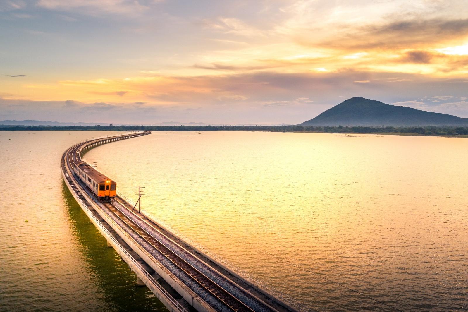 夕暮れの湖を走る列車 タイの鉄道風景