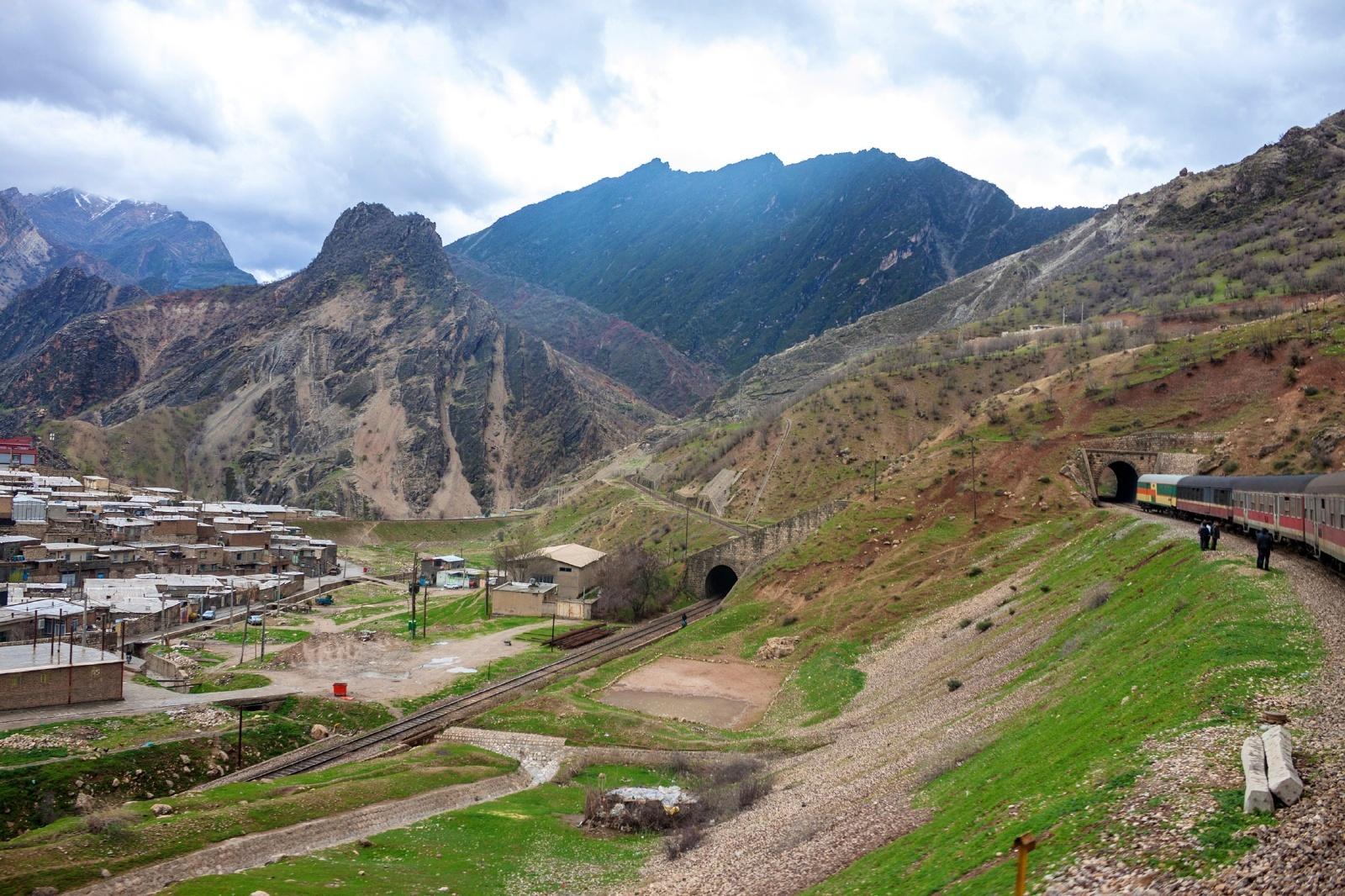 ザグロス山脈の麓の村を行くイランの鉄道 イランの鉄道風景
